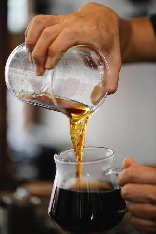 Crop anonymous male barista brewing and pouring aromatic hot coffee from pitcher into glass pot during work in cafe