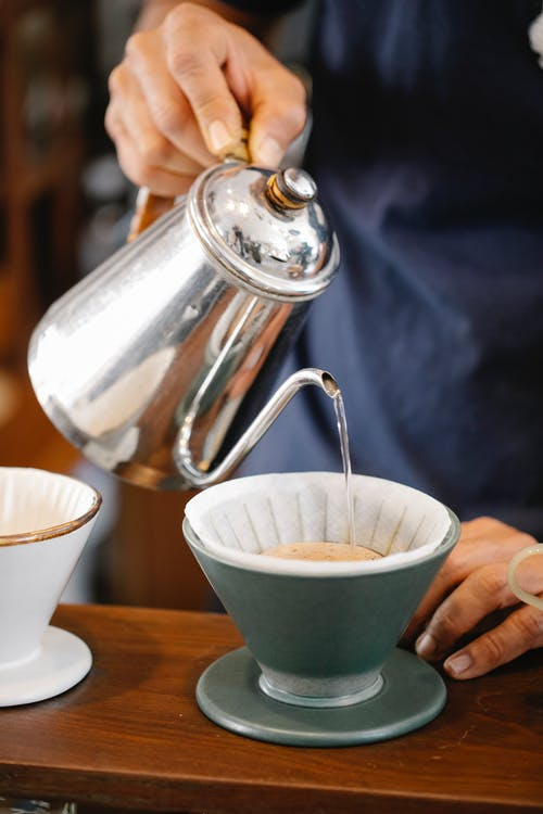 Crop anonymous male barista filling hot water from metal kettle into cup while preparing aromatic pour over coffee in cafe