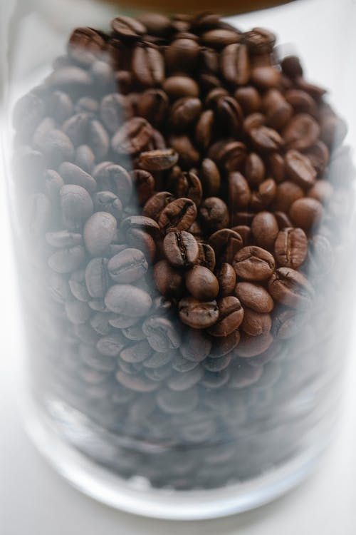 Glass jar with heap of roasted coffee beans