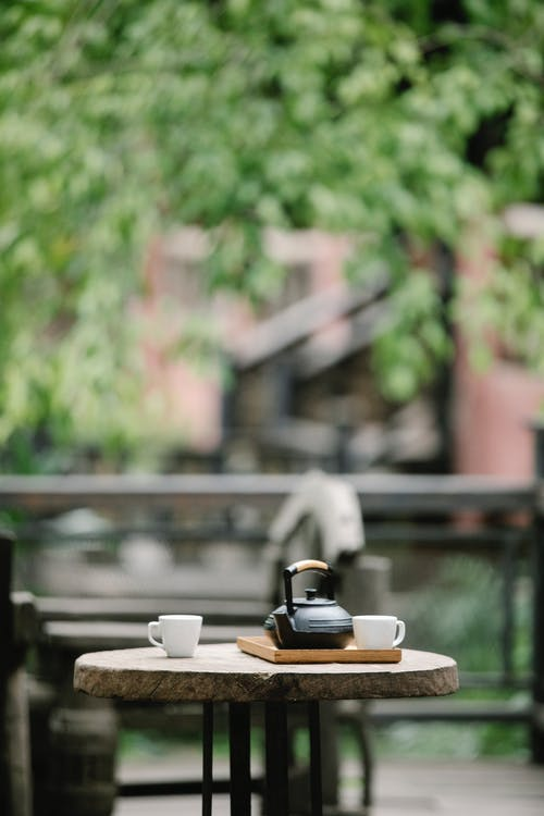 Ceramic cups and pot served on wooden tray on small round table on terrace of cafe in daytime