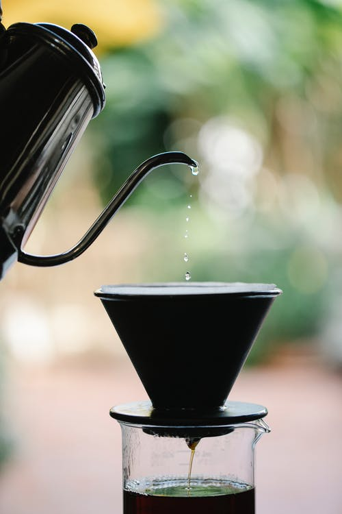 Anonymous person brewing pour over coffee while filling water from kettle into glass coffeemaker in green garden