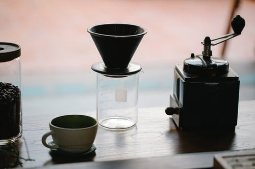 From above of manual coffee grinder with pour over coffeemaker placed in wooden table with ceramic cup and glass jug with roasted beans in morning