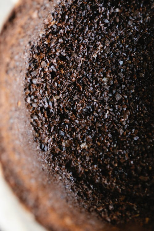 Top view closeup of aromatic roasted ground coffee in cup with paper filter in daylight
