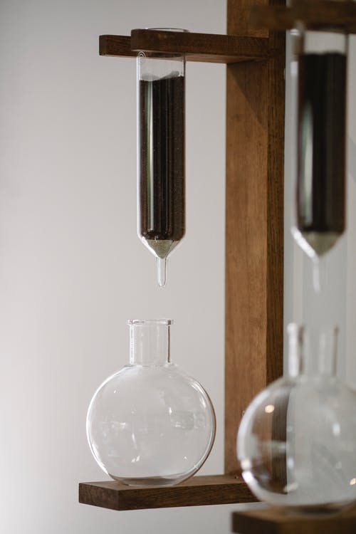 Ground coffee in transparent flask above glass carafe during brewing with Kyoto dripper against white background