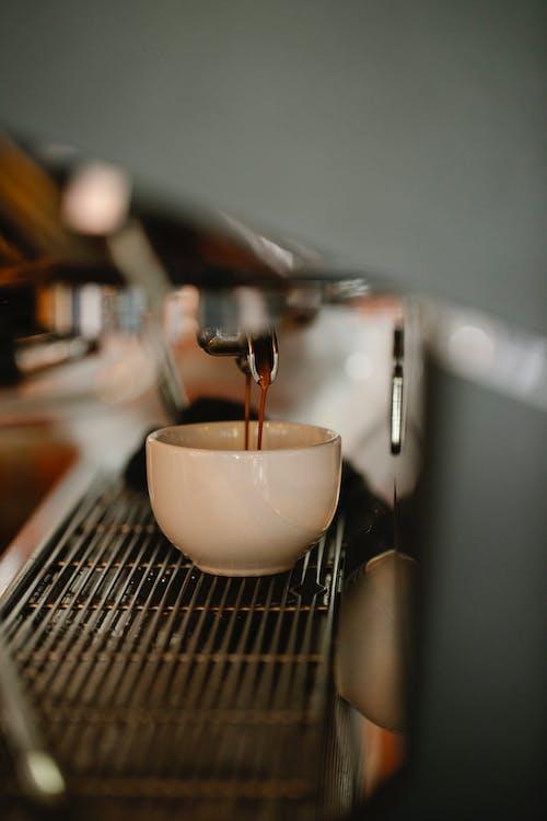 Modern coffee machine preparing double shot espresso pouring in white ceramic cup in cafe