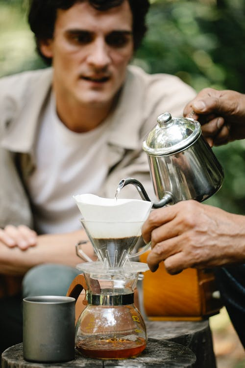 Curious male observing anonymous man pouring hot water from kettle into dripper while making pour over coffee on terrace of cafe on blurred background