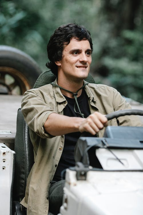 Cheerful man driving car in woodland
