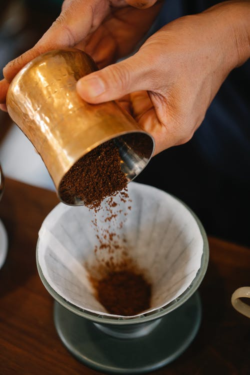 From above of crop anonymous male pouring ground coffee into dripper with filter while making pour over coffee in cafe on blurred background