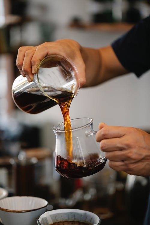Unrecognizable bartender pouring coffee in cafe