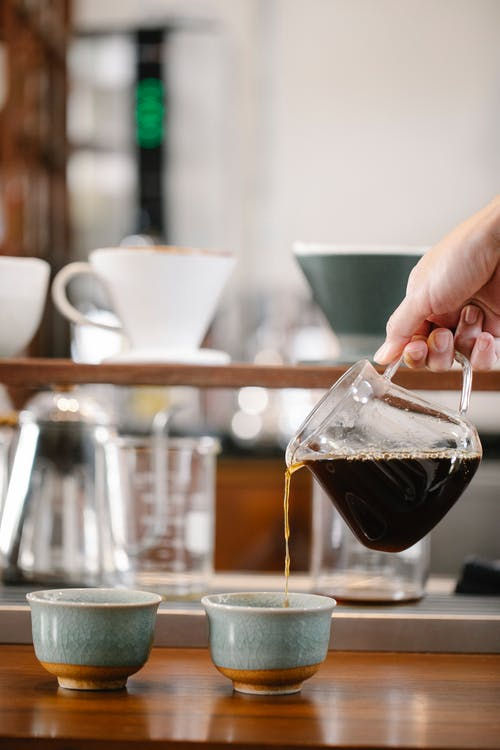 Crop anonymous barista pouring freshly brewed coffee from glass pot into mug in coffee shop with drippers on blurred background