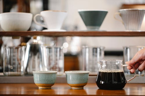 Crop anonymous barista putting glass pot with coffee on table with cups near beakers and drippers on blurred background in modern cafe