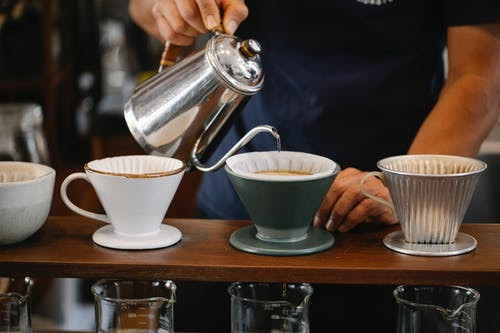 Faceless barista pouring water in dripper
