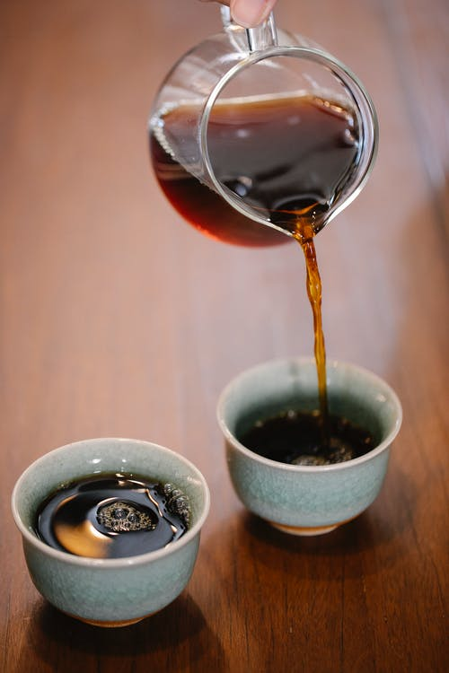 Crop anonymous person pouring freshly brewed aromatic coffee from glass pot into mugs served on wooden table in modern cafe