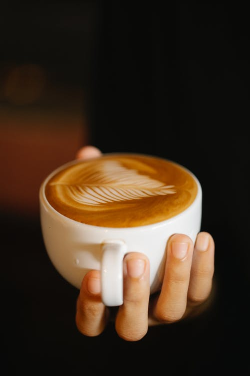 Faceless barista with cup of latte