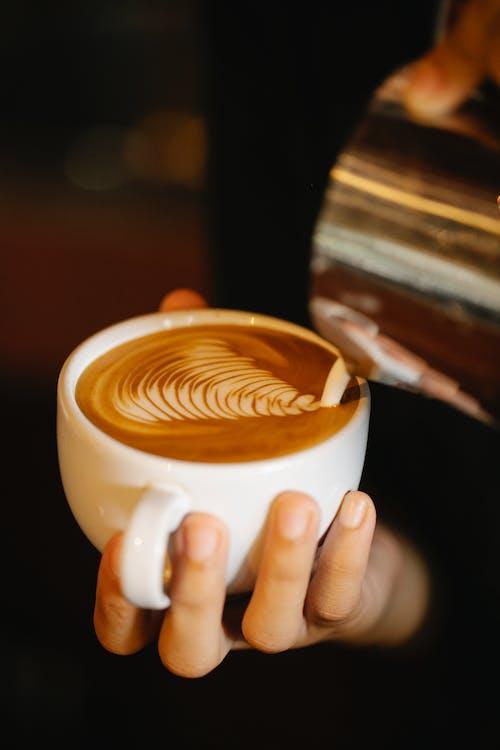 Faceless barista making latte art
