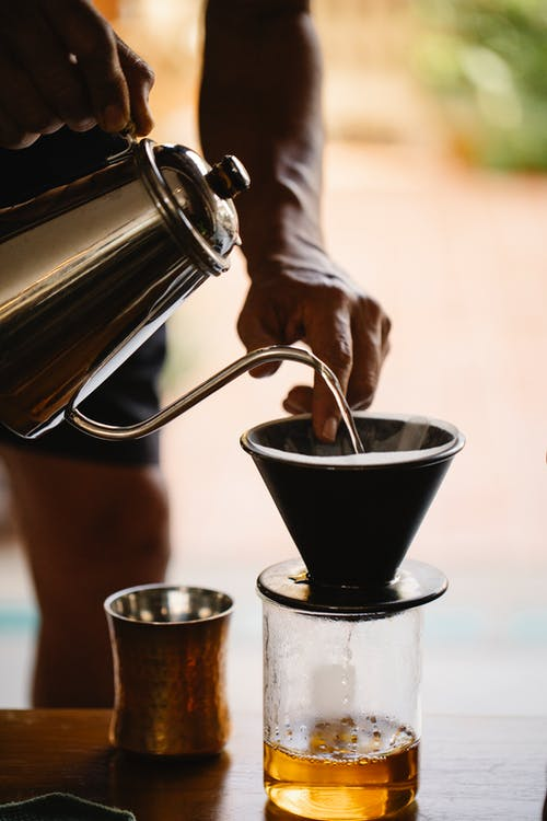 Crop barista pouring hot water from kettle into dripper while preparing alternative pour over coffee