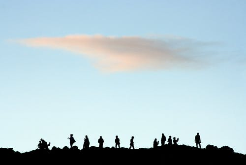 Silhouette of People Standing on Rock