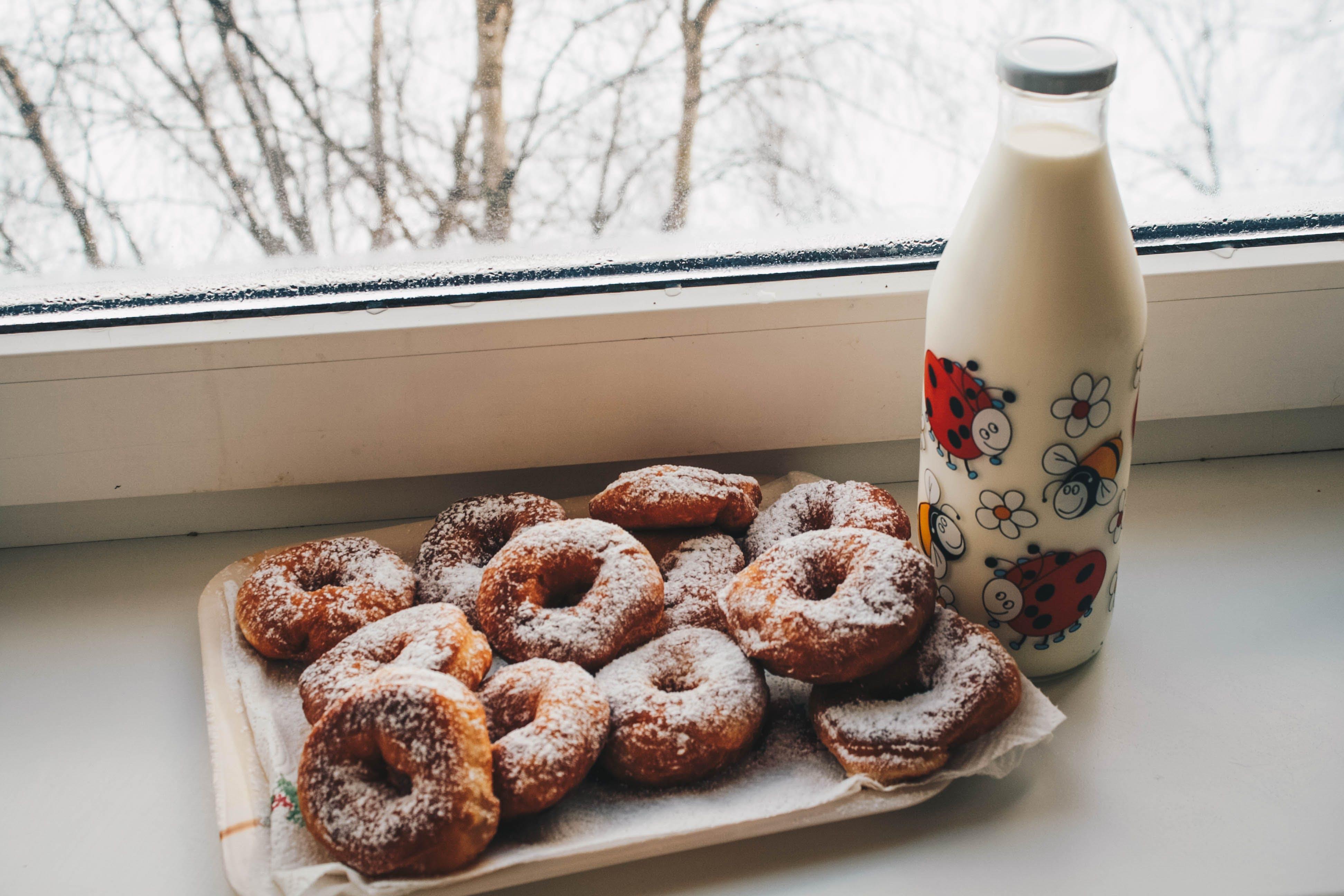 Doughnuts and Milk Bottle Near Clear Glass Window