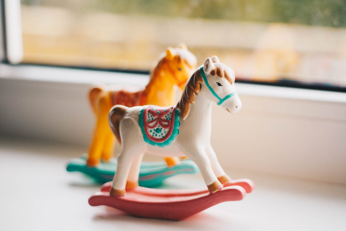 Small toy horses for kids on windowsill