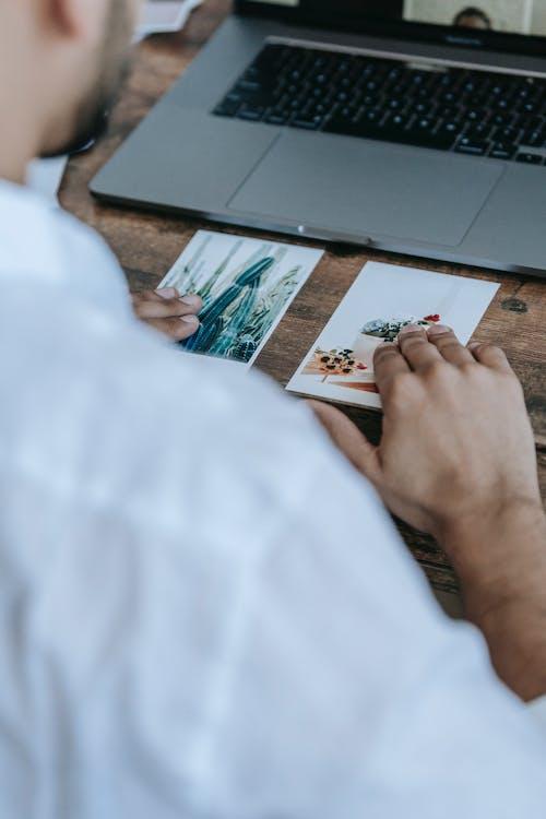 Crop unrecognizable man looking at printed photos at desk