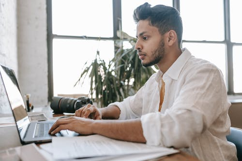Side view attentive young ethnic male photographer wearing white shirt editing photos on modern netbook while sitting at desk with professional photo camera
