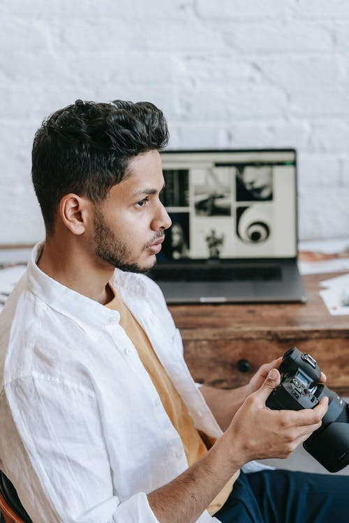 Thoughtful ethnic man with professional photo camera sitting at desk
