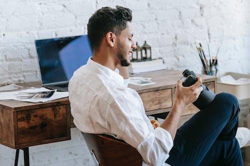 Cheerful ethnic man using photo camera in light office