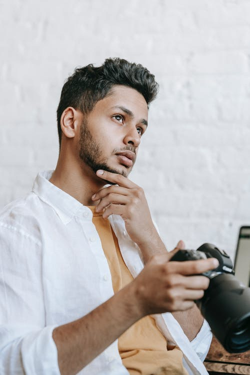 Pondering young ethnic male in casual clothes holding professional photo camera and touching chin in contemplation while looking away and sitting in light room