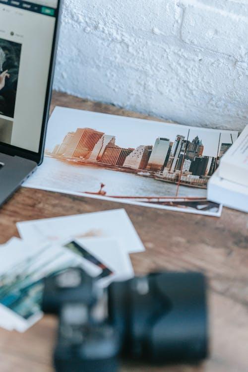 Images scattered on desk near laptop