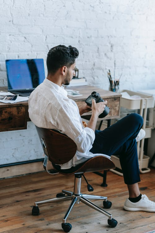Back view focused young male photographer in casual clothes using modern professional photo camera while sitting with legs crossed near desk with laptop
