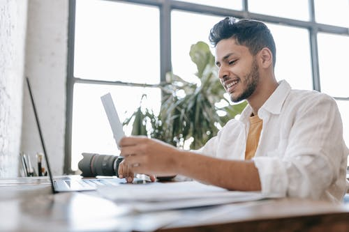 Happy ethnic man looking at printed picture at desk