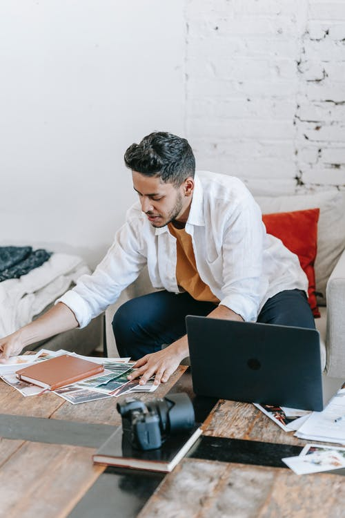 Young ethnic male photographer scattering printed documents on table near netbook and professional photo camera in living room