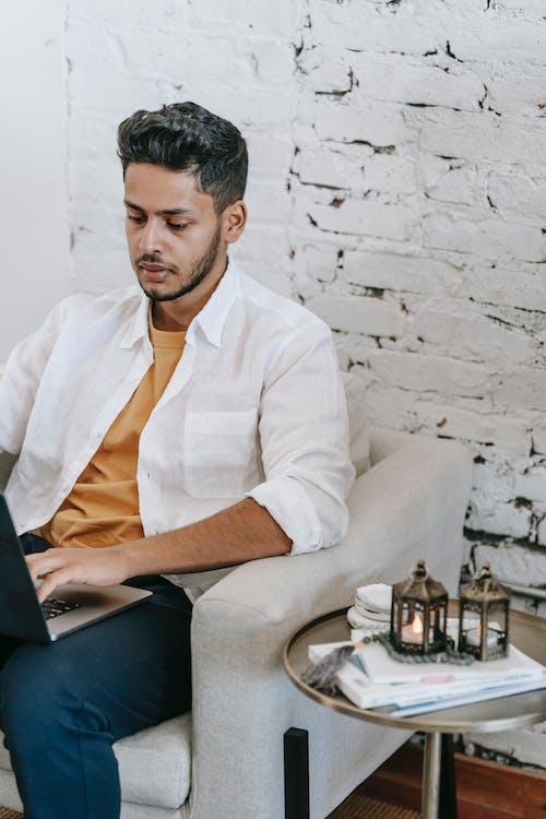 Focused ethnic man working on laptop on cozy armchair