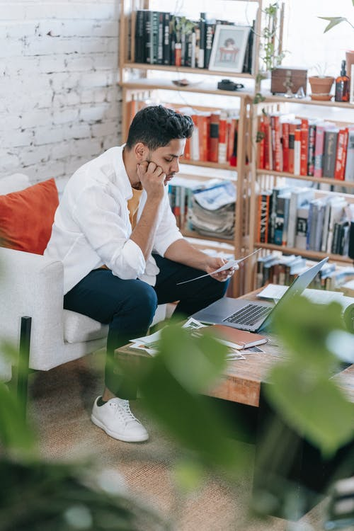 Concentrated ethnic male wearing casual outfit reading document and leaning on hand while sitting on armchair near table with netbook in light living room