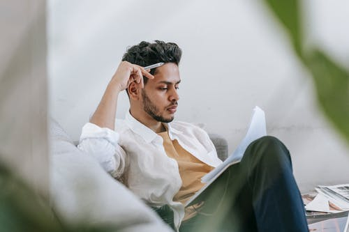 Concentrated ethnic male in casual clothes reading notes in diary while sitting on cozy sofa in living room