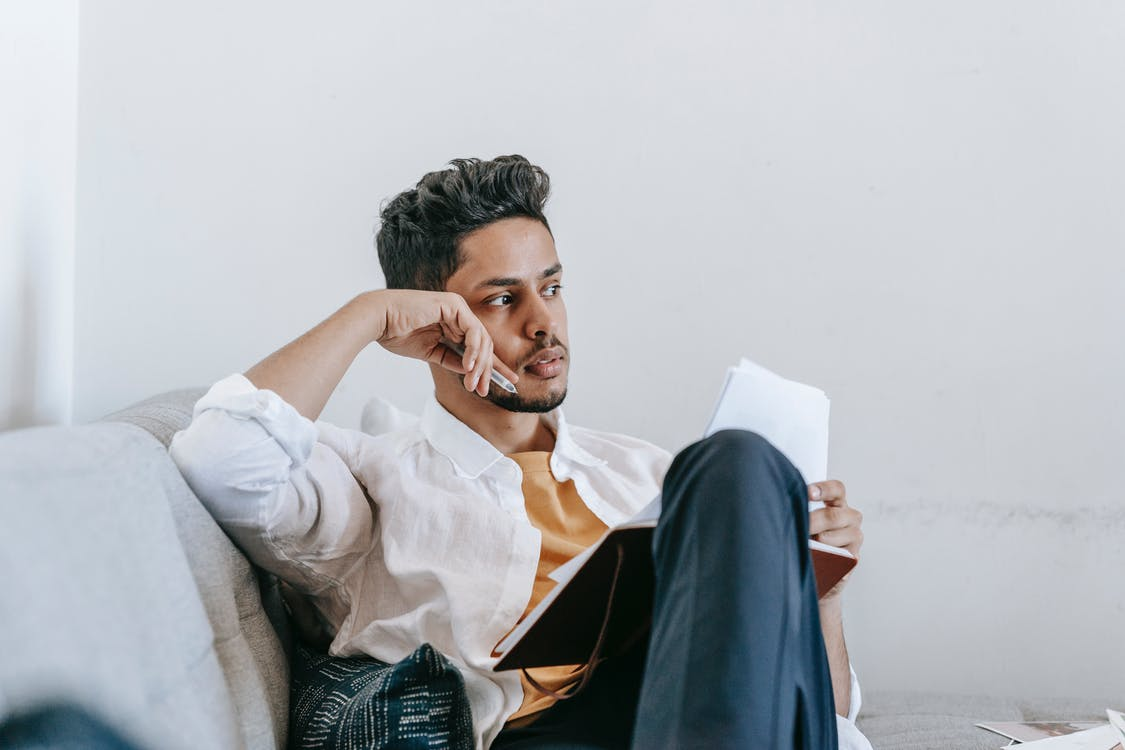 Unemotional ethnic man sitting on sofa with diary