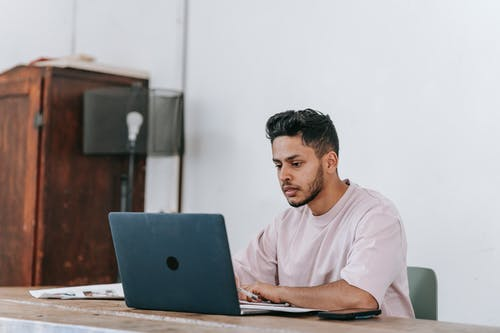 Serious Hispanic freelancer working on laptop at table in house
