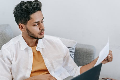 Serious ethnic man reading document and using laptop on sofa