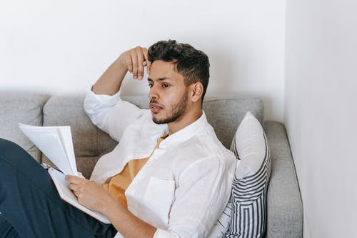 Concentrated young ethnic male wearing casual clothes reading documents and diary and touching head while resting on sofa and looking away