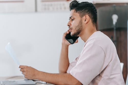 Side view thoughtful ethnic male in casual shirt reading document and talking on mobile phone while sitting at desk