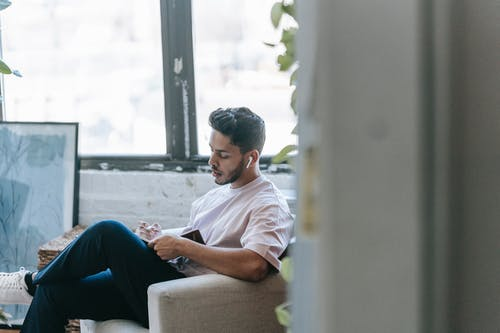 Pensive young ethnic male in casual wear writing in diary and listening to music via earbuds while sitting in cozy armchair