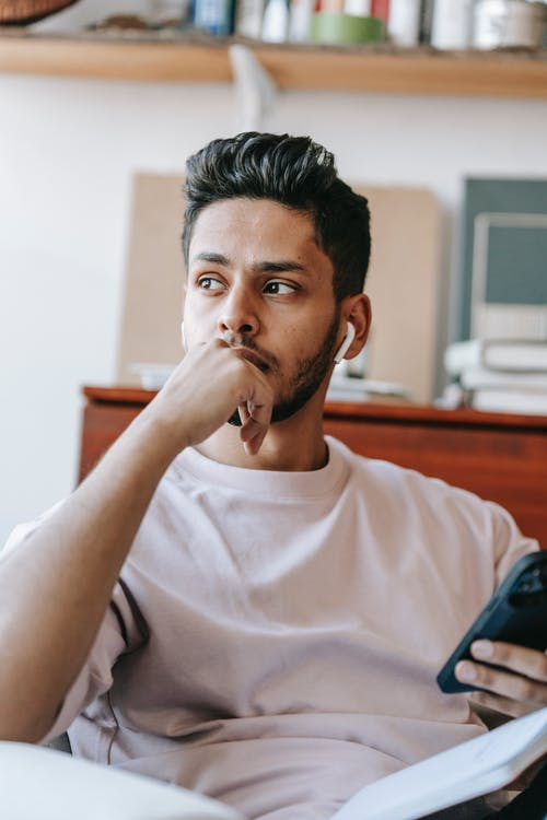 Pensive young ethnic male wearing casual outfit and earbuds browsing cellphone and looking away thoughtfully while sitting on armchair and touching chin