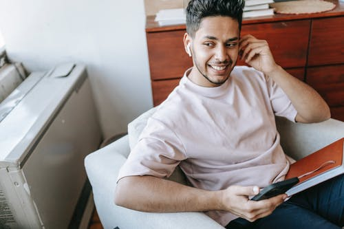Happy ethnic man in earbuds browsing smartphone in armchair
