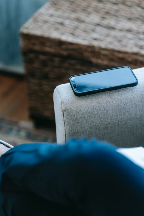 Modern smartphone placed on armchair arm