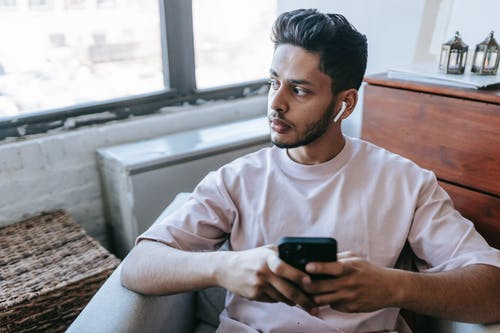Focused bearded Indian male looking away and listening to music in wireless earphones while texting message on cellphone in armchair