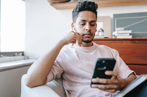 Thoughtful Indian man with wireless earbuds messaging on smartphone