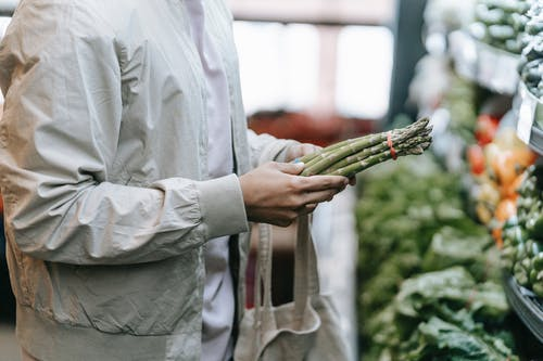 Crop faceless buyer with shopping bag picking green asparagus while standing near stall with fresh greens in supermarket on blurred background