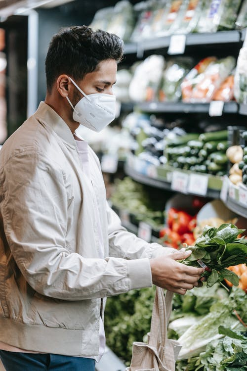 Serious Indian man in protective mask choosing greens in supermarket