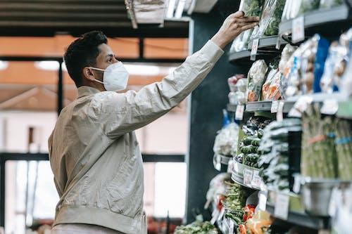 Indian man choosing groceries in supermarket