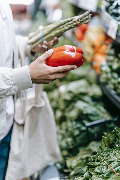Unrecognizable customer choosing vegetables in supermarket